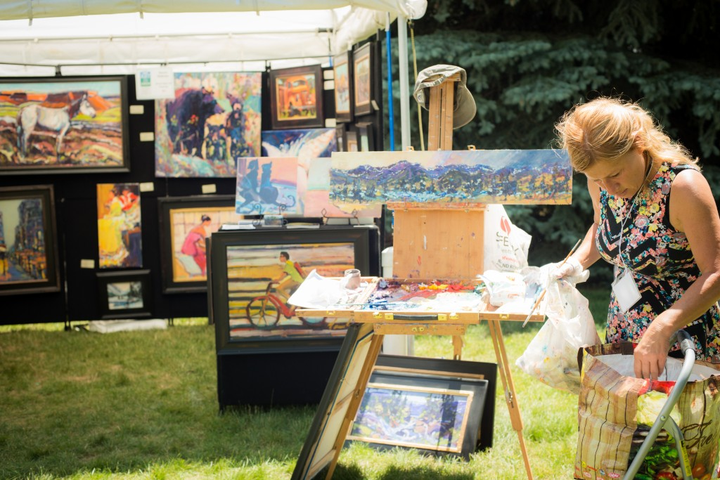 Shopper browsing art at Art on the Green in Lyons, Colorado.