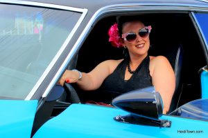 pinup poses inside a retro car at Hot Cars Cool Nights. HeidiTown.com